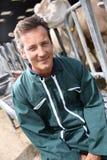 Agriculteur heureux s'asseyant dans la grange Images stock
