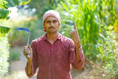 Agriculteur indien avec des faucilles dans son domaine photographie stock