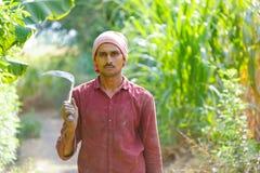 Agriculteur indien avec des faucilles dans son domaine image stock