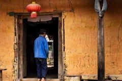 Agriculteur méconnaissable de hmong entrant dans une maison traditionnelle de hmong avec une lanterne chinoise accrochant dans la photos libres de droits