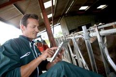 Agriculteur moderne à l'aide du comprimé dans la grange Photographie stock libre de droits