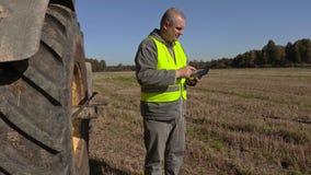 Agriculteur près de tracteur avec le PC de comprimé banque de vidéos
