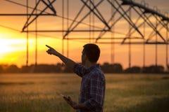 Agriculteur regardant le système d'irrigation dans le domaine le coucher du soleil image stock