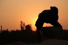 Agriculteur travaillant dans un domaine de riz dans le coucher du soleil Image stock
