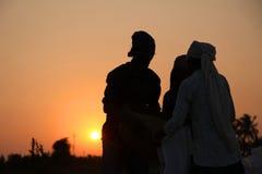 Agriculteur travaillant dans un domaine de riz dans le coucher du soleil Image libre de droits