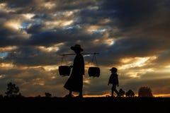 Agriculteurs marchant au coucher du soleil Photo stock