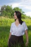 Agricultrice dans un domaine parmi l'herbe verte Photographie stock libre de droits