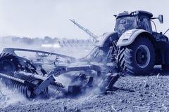 Agricultura El tractor prepara la tierra para sembrar y el culto Foto de archivo libre de regalías