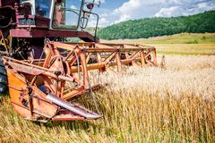 Agricultural activities with vintage harvesting machine Royalty Free Stock Photo