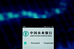 Agricultural Bank of China logo on smartphone. Ivano-Frankivsk, Ukraine - May 22, 2019: Agricultural Bank of China logo is seen on an smartphone over stock chart stock photos