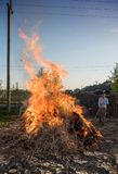 Work in the garden. Farmer burning dried branches royalty free stock photography
