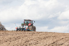 Agricultural drill or planter on a hilltop skyline with ploughed Royalty Free Stock Image