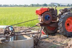 Agricultural engine pumping into rice paddy fields. The orange engine used in agriculture is pumping water from the groundwater well to nourish the rice in the Royalty Free Stock Images