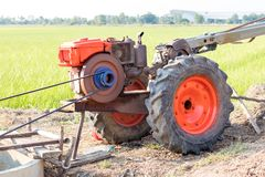 Agricultural engine pumping into rice paddy fields. The orange engine used in agriculture is pumping water from the groundwater well to nourish the rice in the Royalty Free Stock Photo
