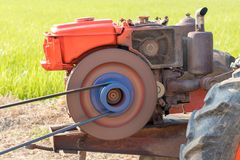 Agricultural engine pumping into rice paddy fields. The orange engine used in agriculture is pumping water from the groundwater well to nourish the rice in the Stock Image