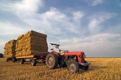 Agricultural Equipment red tractor with straw on t Stock Photos