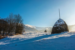 Agricultural field with haystack on hillside in winter. Stack of hay on a snowy hillside meadow in mountain area in winter Royalty Free Stock Images