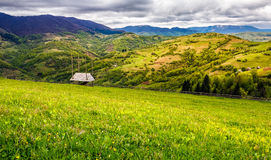 Agricultural field in mountains. Agricultural hay field in mountains. woodshed and fence on the grassy meadow. beautiful rural landscape Stock Images