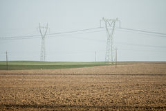 Agricultural field , with pylons Royalty Free Stock Images
