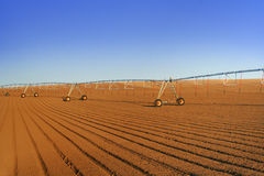 Agricultural Field Sprinkler. An industrial agriculture farm irrigation pivot sprinkler stretches off into the distance in a newly plowed field under a clear Royalty Free Stock Photo