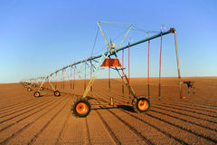 Agricultural Field Sprinkler. An industrial agriculture farm irrigation pivot sprinkler stretches off into the distance in a newly plowed field under a clear Stock Photos