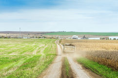 Agricultural field with tractor trailer traveling on the road to the farm Royalty Free Stock Image
