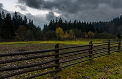 Agricultural fields in forest on cloudy day. Wooden fences among agricultural fields in forest on cloudy autumn day stock image