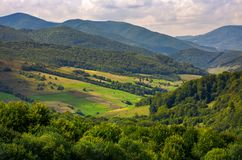 Agricultural fields on grassy hills in mountains. Beautiful rural landscape of Carpathians royalty free stock image