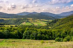 Agricultural fields on grassy hills in mountains. Beautiful rural landscape of Carpathians Stock Photos