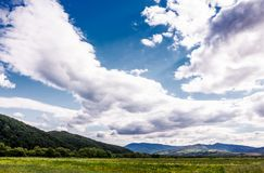 Agricultural fields in mountainous countryside. Lovely landscape with gorgeous cloudy sky Royalty Free Stock Photo