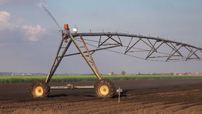 Agricultural Irrigation Sprinklers Irrigating Cultivated Farming Field Land Soil on a Bright Sunny Day stock video footage