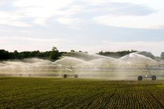 Agricultural irrigation system on a farmers field. Agricultural irrigation system watering a growing farmers crop stock photo
