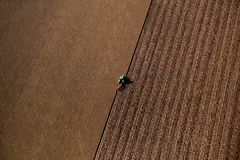 Agricultural knitting. Tractor from above in agricultural landscape Stock Photography