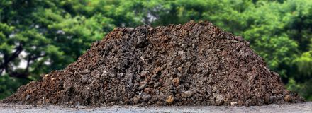 Agricultural land for cultivation, A large pile of thick, Wet brown soil mountain shape, Clay pile isolated tree nature Background. The Agricultural land for Royalty Free Stock Images