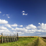 Agricultural landscape. Scenic view of agricultural field and wooden fence in countryside under cloudscape Stock Photos
