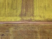 Agricultural landscape from air. Straight narrow ground road between sunny green and brown fields.  royalty free stock photography
