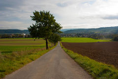 An agricultural landscape in Bad Pyrmont, Germany. A landscape with agricultural fields, a road, trees and hills and a small town on the background. Location Stock Photography