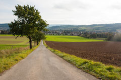 An agricultural landscape in Bad Pyrmont, Germany. A landscape with agricultural fields, a road, trees and hills and a small town on the background. Location Royalty Free Stock Photography