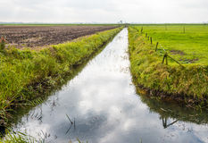Agricultural landscape diagonally divided by a ditch Royalty Free Stock Image