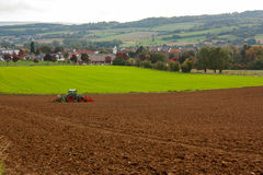 An agricultural landscape. Agricultural fields and a tractor plowing the soil. Location Bad Pyrmont, Germany Royalty Free Stock Photography