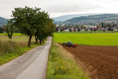 An agricultural landscape. Agricultural fields, a tractor plowing the soil, a road going in the direction of a town and trees. Location Bad Pyrmont, Germany Royalty Free Stock Images