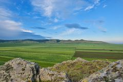 Agricultural landscape with hills under a blue summer sky.  Royalty Free Stock Images