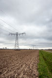Agricultural landscape with a row of electricity pylons Royalty Free Stock Photo