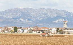 Agricultural landscape with tractor plowing. Royalty Free Stock Image