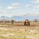 Agricultural landscape with tractor plowing. Stock Photo