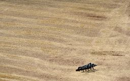 Agricultural machine in field. Aerial view of agricultural machine in barren, dry field Stock Photography