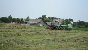 Agricultural machine hay. Heavy agricultural machines tractors preparing hay for animal food fodder in field  circa June 2013 in Zibalai, Lithuania stock video