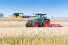 Agricultural machineries in the field. Tractor and combine harvester working in rapeseed field in summer time Stock Image