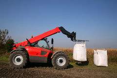 Agricultural machinery with bag of weath seeds. Agricultural forklift is transporting wheat seeds in the giant bag at the field Stock Photography