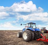 Agricultural machinery cultivates the field. Tractor working on the farm, a modern agricultural transport, a farmer working in the field, fertile land, tractor Royalty Free Stock Images